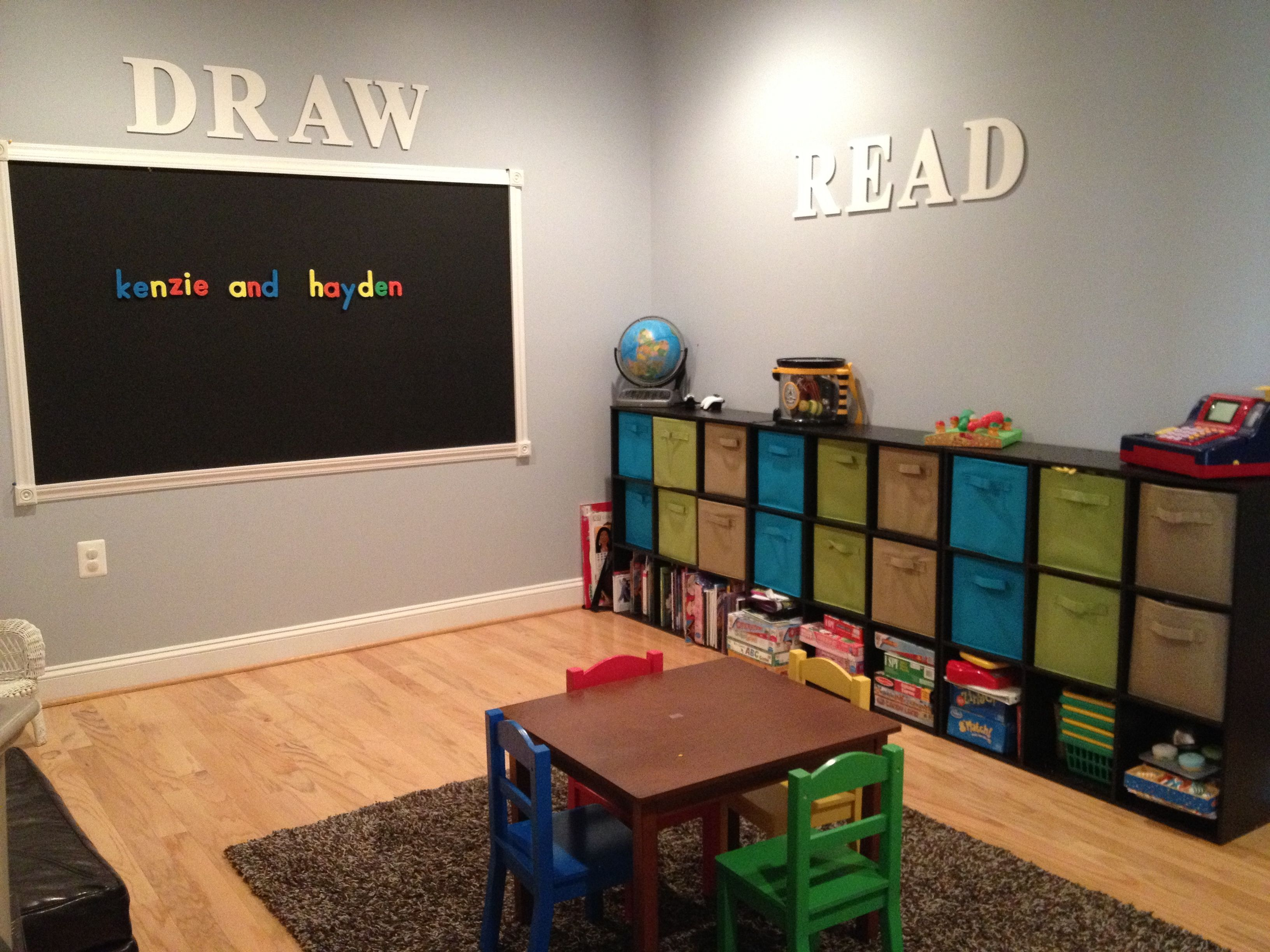 playroom with cube storage bins and magnetic chalkboard