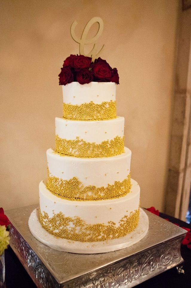 Four tier white wedding cake with gold edible beads, red roses and ...