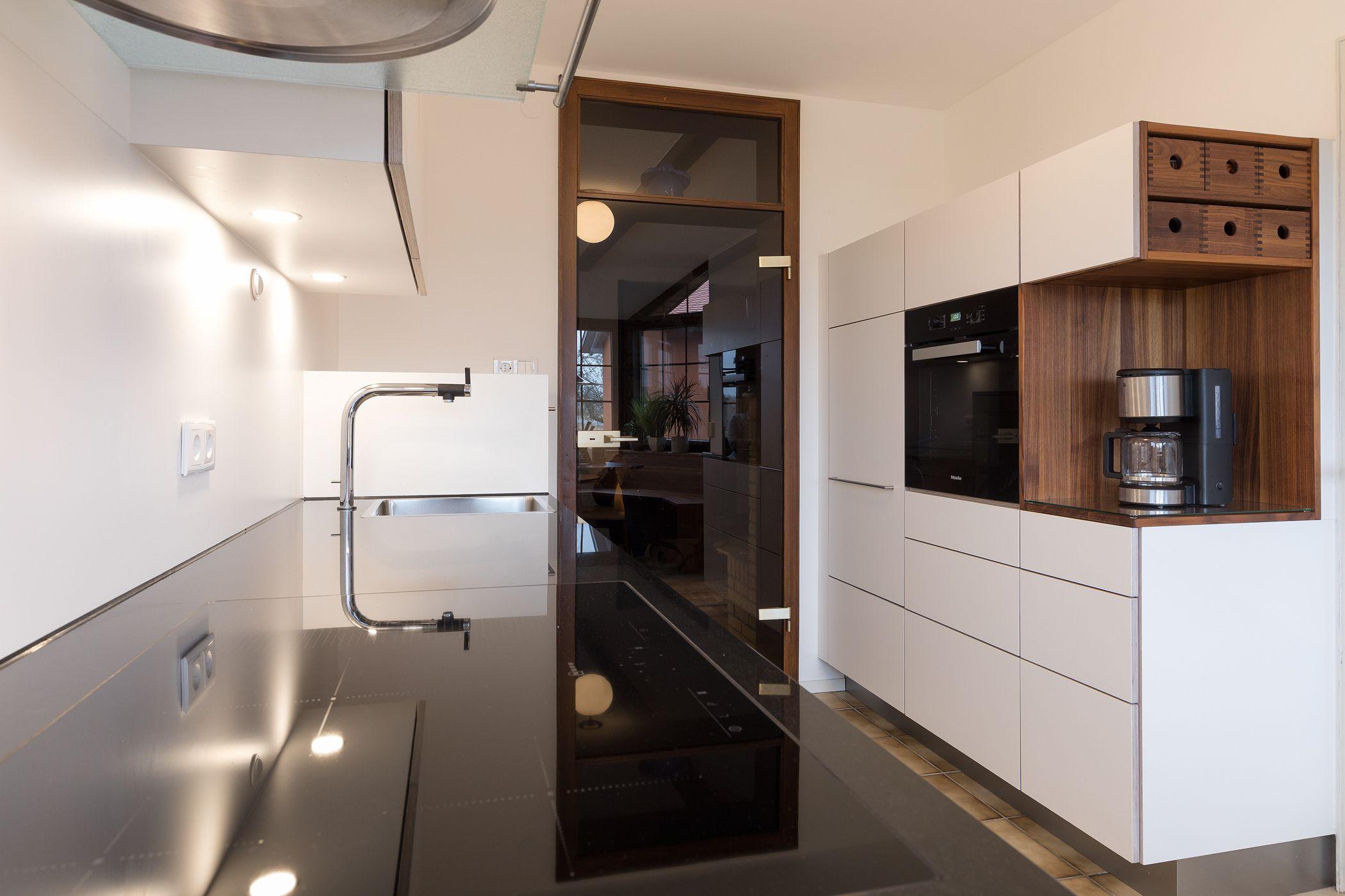 Weiße Küche mit grifflosen Fronten und dunkler Arbeitsplatte ...