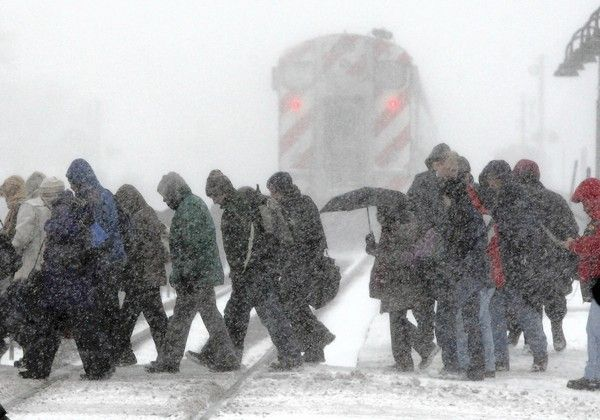 Commuters make their way across the tracks after getting off a westbound Metra train during blizzard winds and cold in Berwyn.