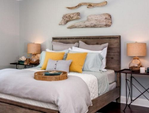 Driftwood above headboard as wall decor in a coastal home for Bedroom designs by joanna gaines