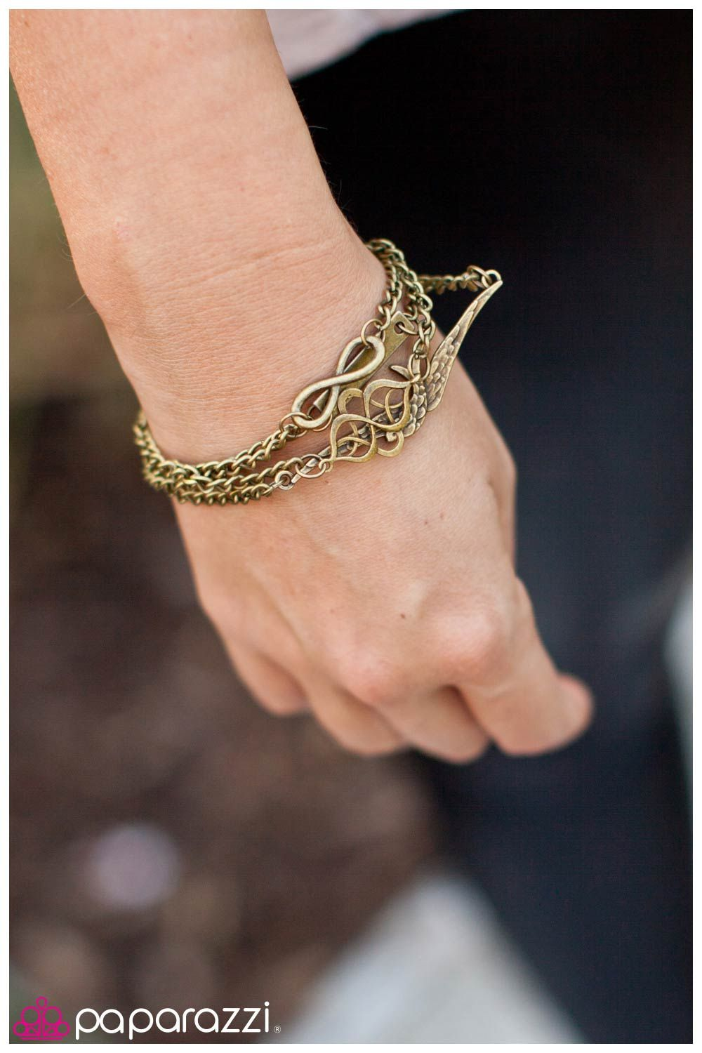 """Then Love Swooped In ~ Four layers of brass chain are embellished with brass charms. Charms include a textured bird, an infinity sign, a filigree-swirled fitting and a rectangular plate with the word """"love"""" etched into the finish. Features an adjustable clasp closure."""