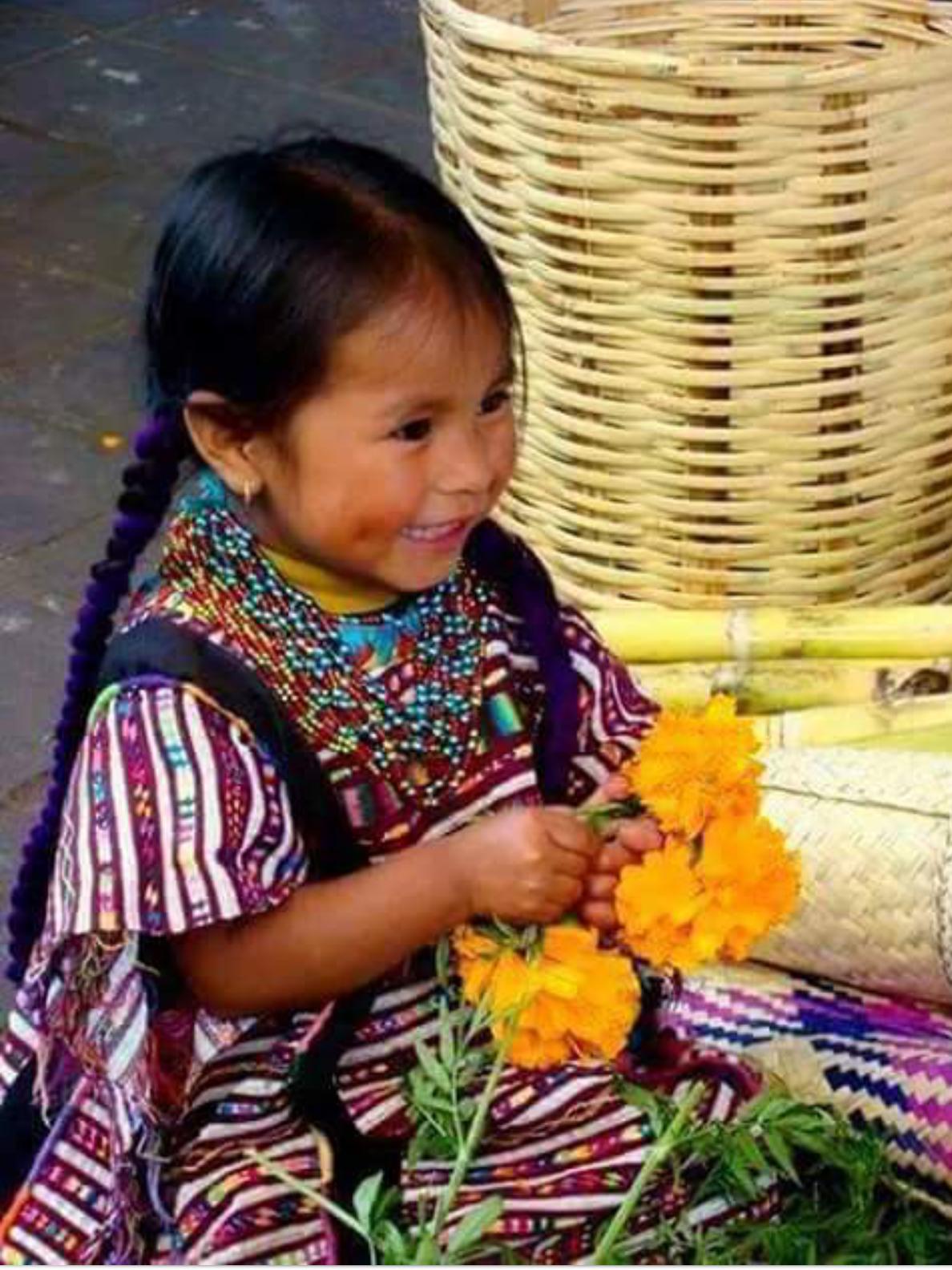 Hermosa niña mexicana jugando con flores de zempaxuchil