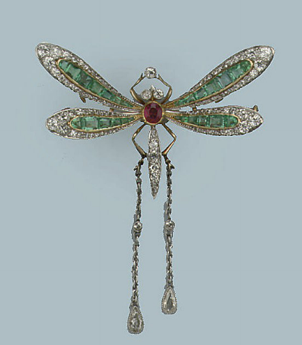 Dragonfly brooch. The wings set with lines of graduated emeralds flanked by cushion-shaped and rodé-cut diamonds to the ruby and diamond set abdomen, supporting two chains terminating in pear-shaped diamond set drops, French marks, circa 1930