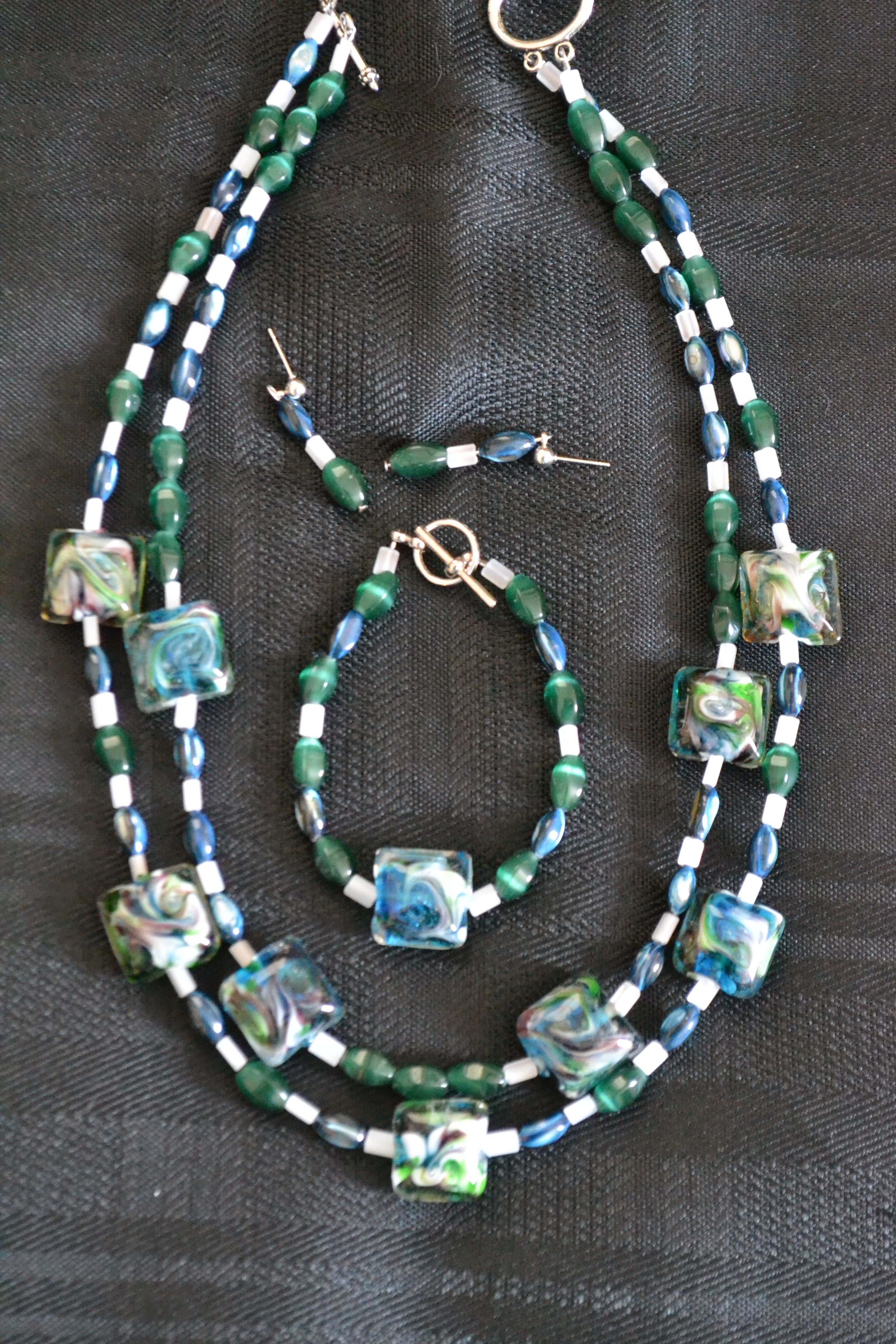 Double strand necklace in blue, green cat's eye and white.  Larger beads of coordinating colors, and hint of plum  included in necklace  Matching bracelet  Coordinating earrings-silver posts with dangle  Items sold separately-Multiple Item Discount!    Earrings-$6  Bracelet-$6  Necklace-$19  Ask about discount for more than one item!