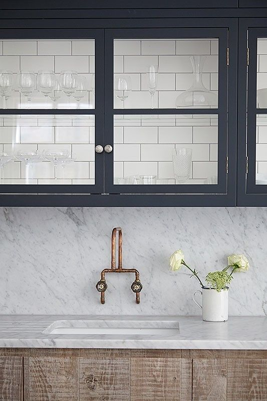 navy blue exposed cabinets with brass hardware and marble countertops