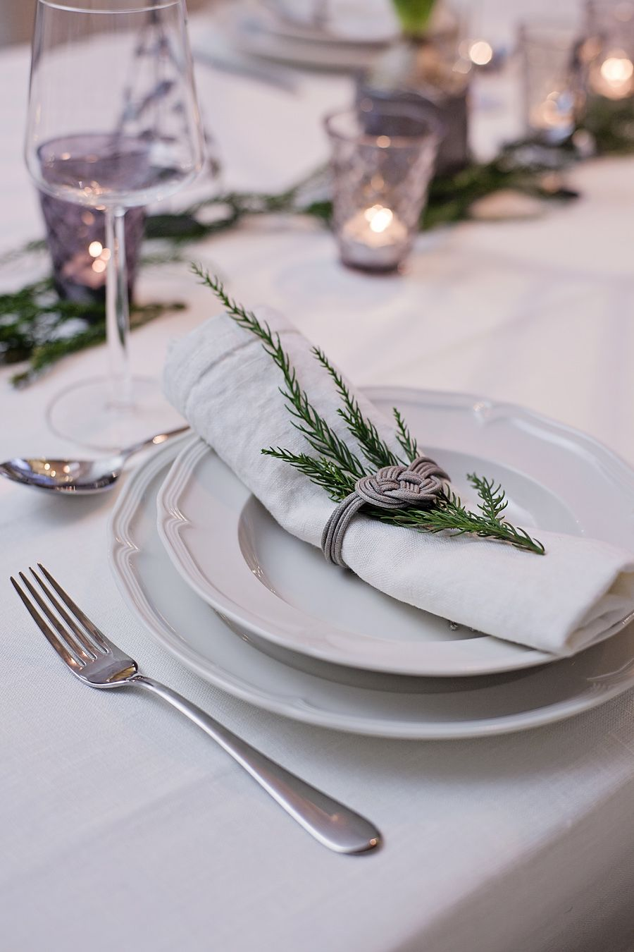 Greenery tucked in with a linen napkin & wrapped with a cord tied in a nautical knot / Photo Krista Keltanen
