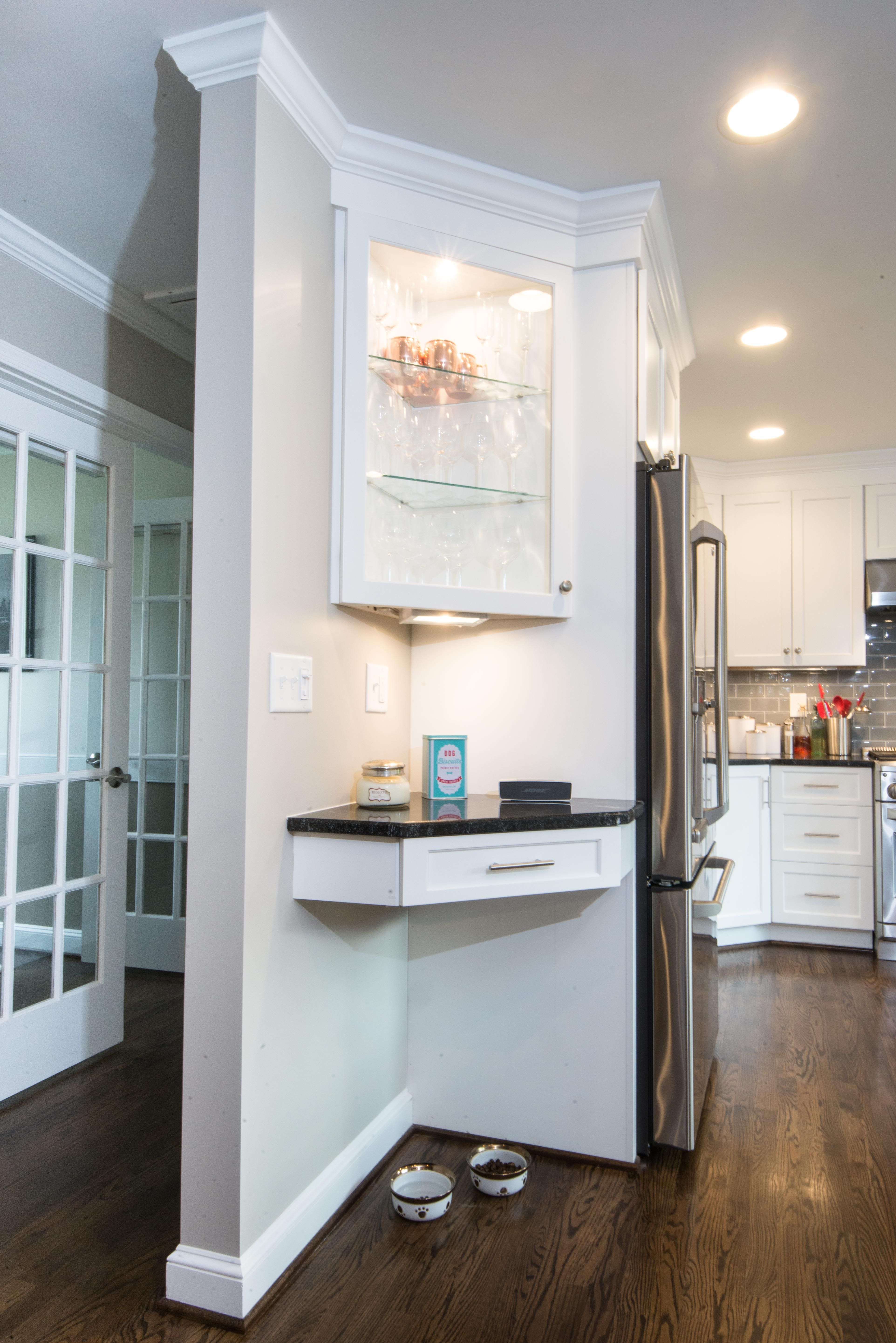 This glass corner cabinet makes a beautiful showcase as you enter the kitchen. The drawer below the landing space is equipped as a charging station for phones, tablets, laptops, iPods, etc. The space below is the perfect niche for the dogs food and water bowls.