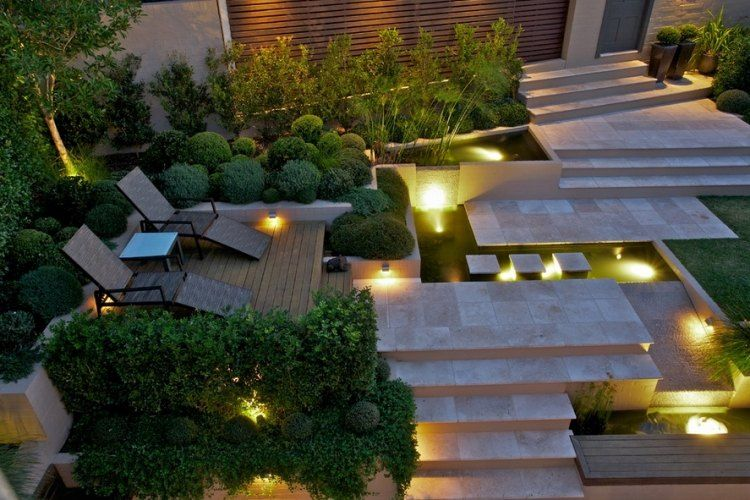 jardin en pente moderne marches en pierre naturelle haie verte arbustes et buis terrasse en bois composite et clairage led