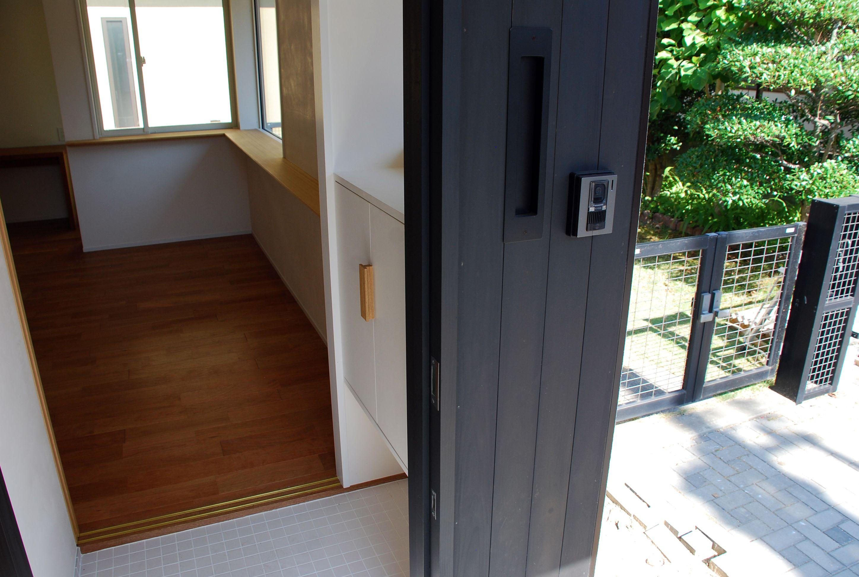 玄関土間と室内床高さは3センチの段差としている 黒塗装の外壁に 白