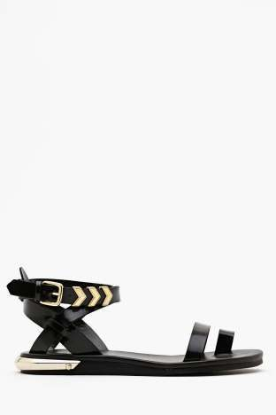 Shoe Cult Zealand Sandal - Black at Nasty Gal. The coolest black faux patent leather sandals featuring a toe strap and buckled ankle strap with gold arrow hardware. Low stacked heel with faceted cap, fully lined. Looks awesome with a crop tee and high-waist shorts! By Shoe Cult.