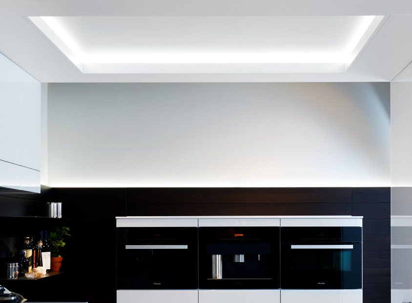 Taking a holistic view of the kitchen and living space means not only the floor and walls, but also the ceiling. The functional arch, with its innovative ceiling element, connects spaces and creates a room within a room.   #Poggenpohl #CoveLighting
