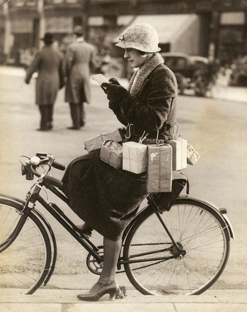 """Shopping Made Easy"" Miss Marsh a south coast resident has devised this novel method of carrying home the parcels when out shopping on her bicycle, by the aid of hooks attached to her back. ~ ~ ~I'm guessing that this is from the 1920s?"