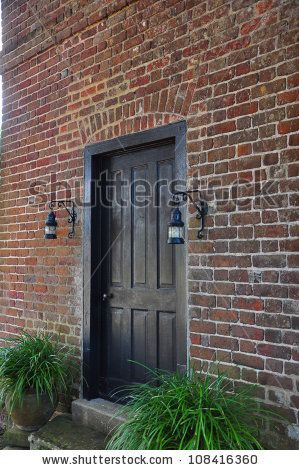 black front door on a red brick housem reel, via shutterstock