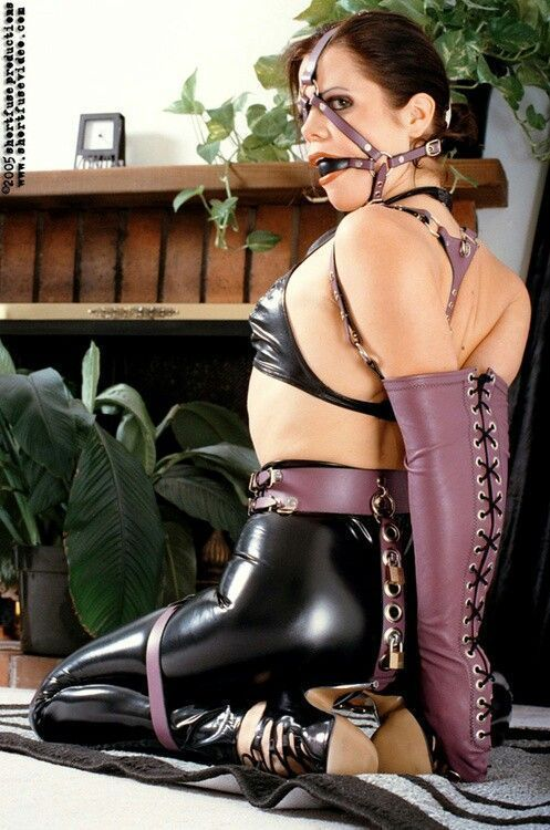 Girl struggeling in leather bondage harness