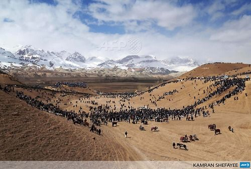 AFGHANISTAN, BAMIYAN CITY : Afghan horsemen and spectators gather on an arid patch of land near snow-capped mountains to play the traditional sport of Buzkashi near Bamiyan city in the central Afghan province of Bamiyan on March 23, 2014. Buzkashi is a centuries-old game where two opposing teams of horsemen compete to throw a goat carcass into a scoring circle.