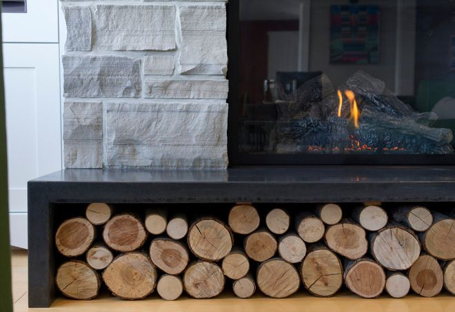 The gas fireplace features a local Bruce Grey ledgerock surround and a long poured concrete hearth. Crisply cut hardwood logs aren't intended for the actual fire; they add a sculptural element and pattern that complement the stone.