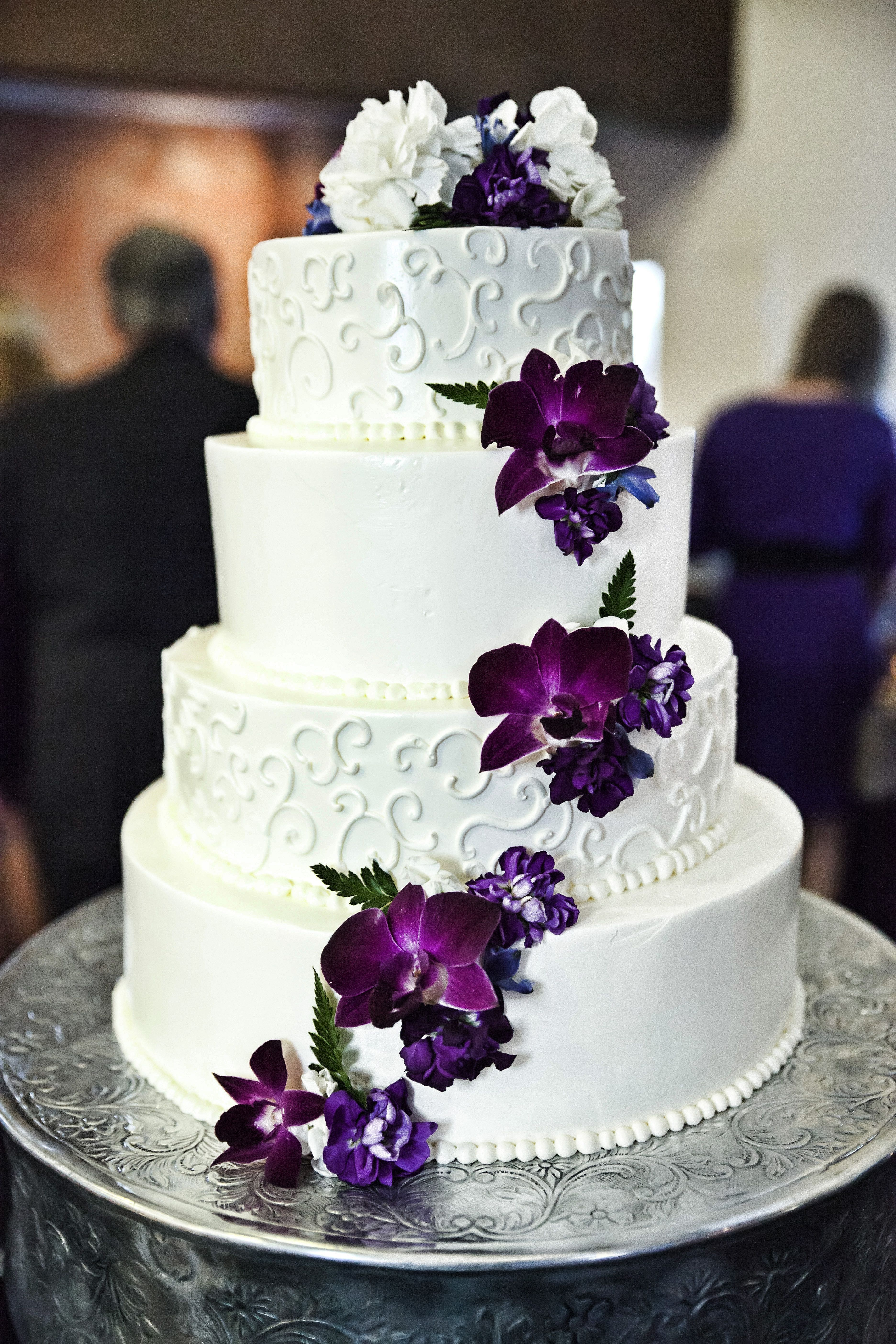 White and purple wedding cake with cascading purple flowers ...