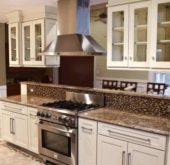 pro range and hood in peninsula built of white shaker cabinets with ...