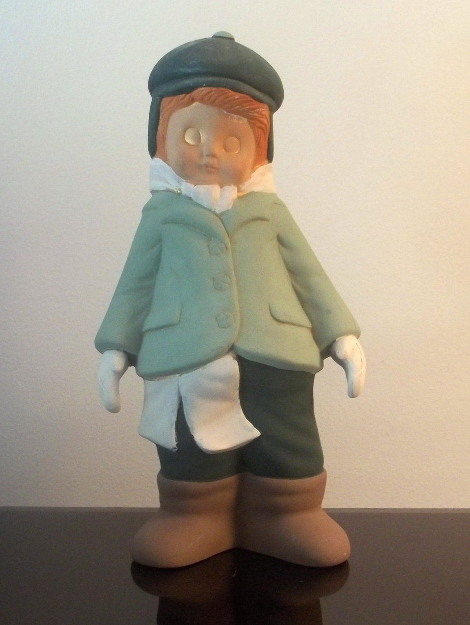 Vintage Christmas Caroler Nicholas 10.5 inches Sugarplum Collection  Beautiful Bisque Christmas Caroler  From the Sugarplum Collection.  This youing boy wears green from head to toe with brown boots and a white scarf and gloves. He stands 10.5 inches high and 5.75 inches wide.  This piece is exquisite and of high quality. Hand painted ceramic bisque. Figure also has sparkles on edges to accent them. See Full Description.