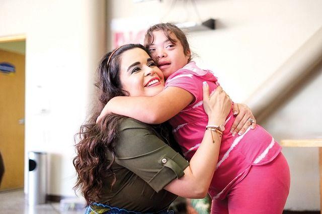 Foto de señora abrazando a una niña con síndrome de Down