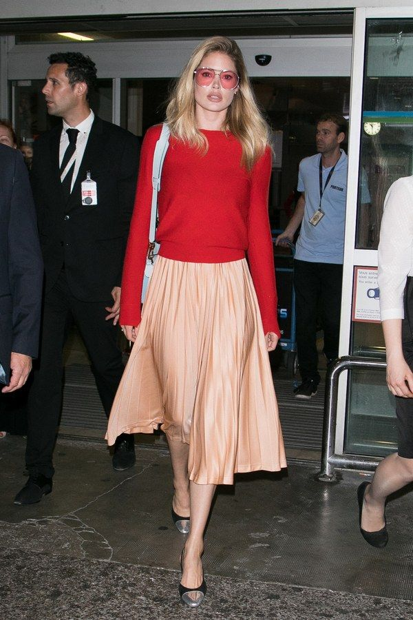 e0b499e079 Doutzen Kroes arrives at the Nice airport wearing an orange pleated skirt,  red sweater, heels, and and pink-tinted aviator sunglasses.