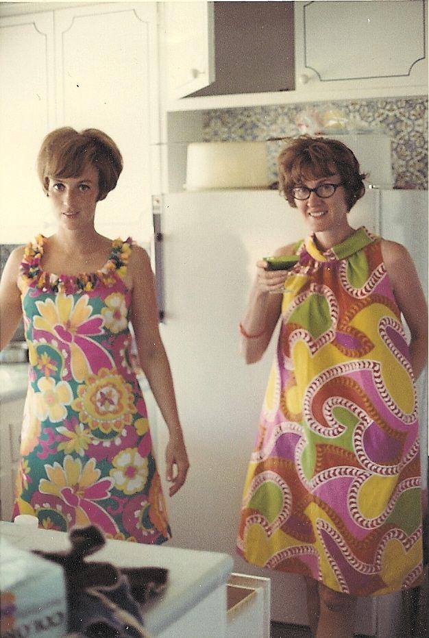 Fantabulous 60s snap. Women in two smashing pysch tent dresses in 60s kitchen