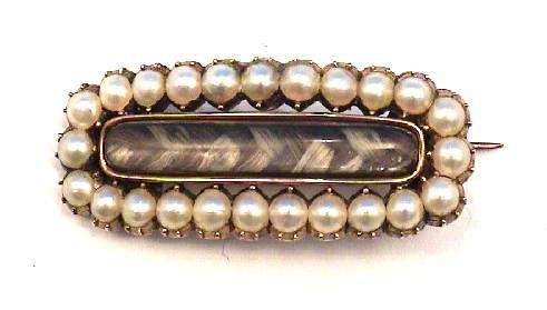 This brooch is from the Georgian era. It features a braid of light and dark hair surrounded by pearls. You can purchase this brooch over at Chancery Lane Antiques on GoAntiques.com for $360-