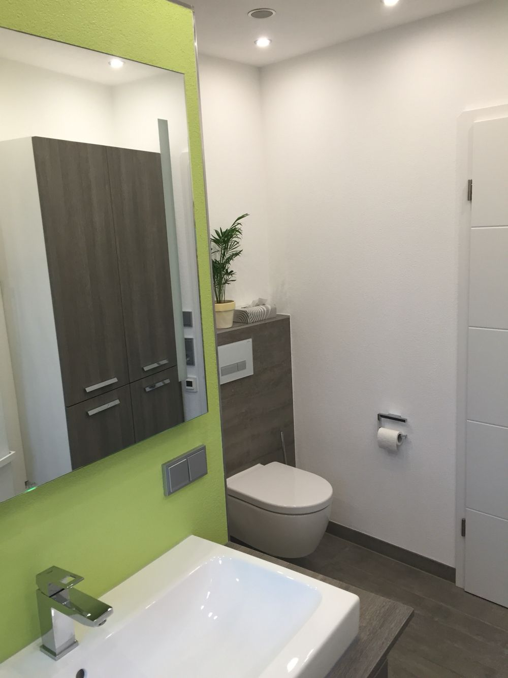 Blick von Waschbecken zum WC. Als Spiegelung ist der ...