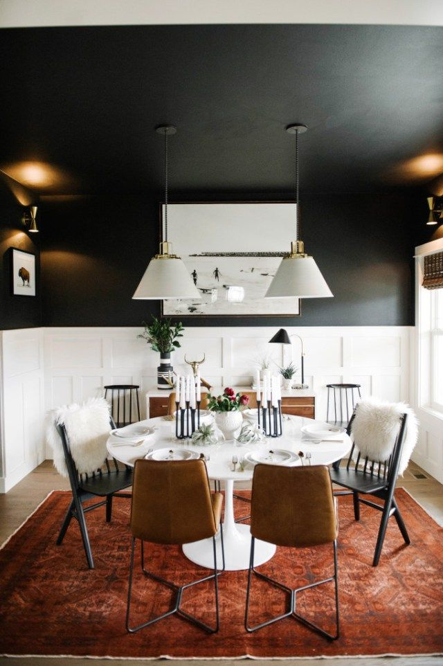 black dining room with white tulip table. mixed dining room chairs