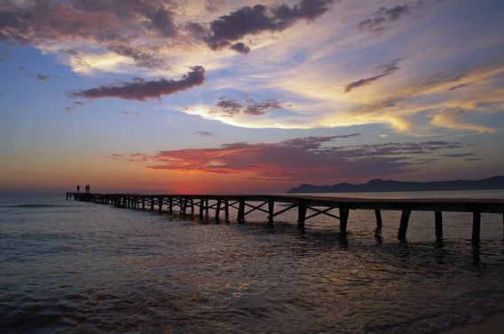 Angler am Steg im Meer vor dem Sonnenaufgang