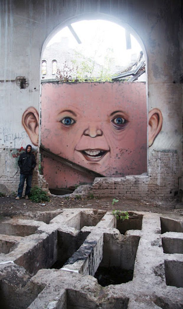 A street artist has brought life to derelict landscapes across Russia by creating quirky faces to run-down buildings.    Nikita Nomerz transforms window frames into eyes and brickwork into teeth and smiles, creating elaborate graffiti with his signature grinning faces through his project, The Living Wall.