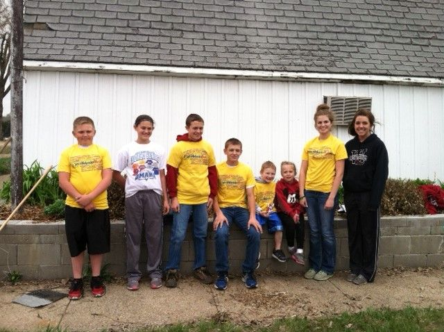 Volunteers from the Westerners 4-H Club in Fullerton, NE helps paint trash barrels and clean off a flower bed for the Nance County Fair.