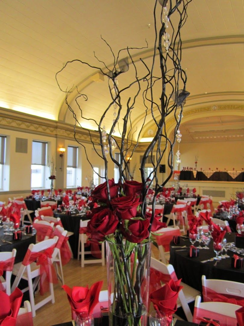 Wedding table centerpieces branches red gold brown willow branch and the other centerpieces were black covered square vases that held black manzanita branches and hanging glass candles with a red rose petals reviewsmspy