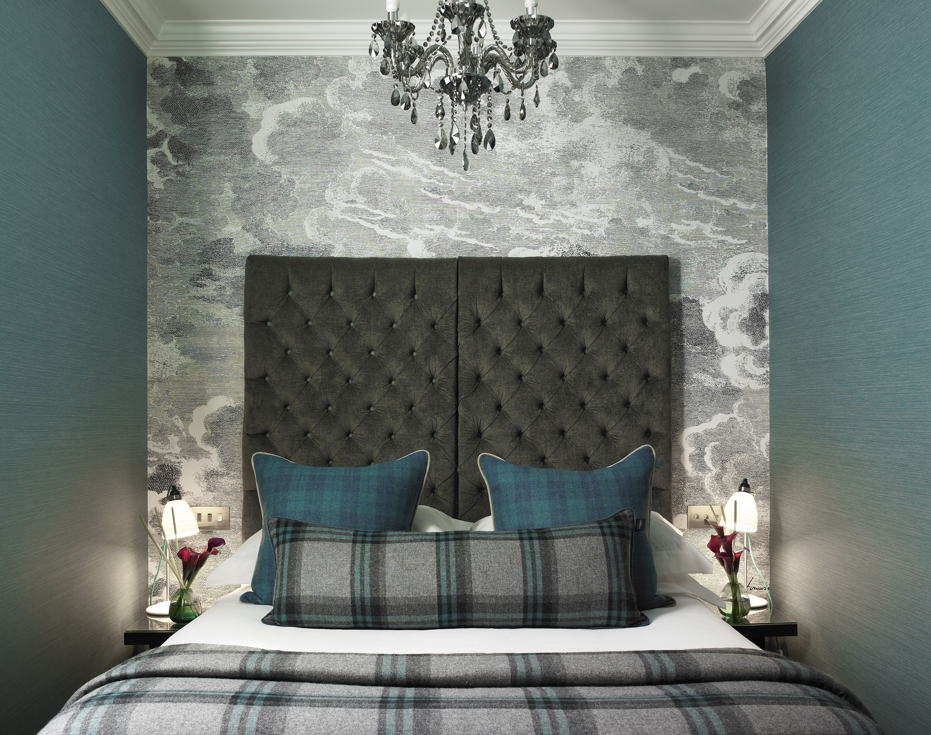 Textured wall covering fabric headboard and hanging lights at the