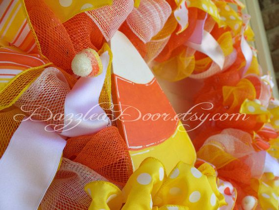Its all about the candy at Halloween and this Candy Corn inspired wreath is bright and full of color to highlight your door and welcome all who visit or come to taste of your treats. Orange deco mesh creates a base for this candy influenced wreath and is then highlighted with white and yellow deco mesh. Glittery candy corns and ribbon adorn and accent this wreath adding to the bright and playful feeling this wreath gives. The final touch is a hand painted wood candy corn and a large, bright…