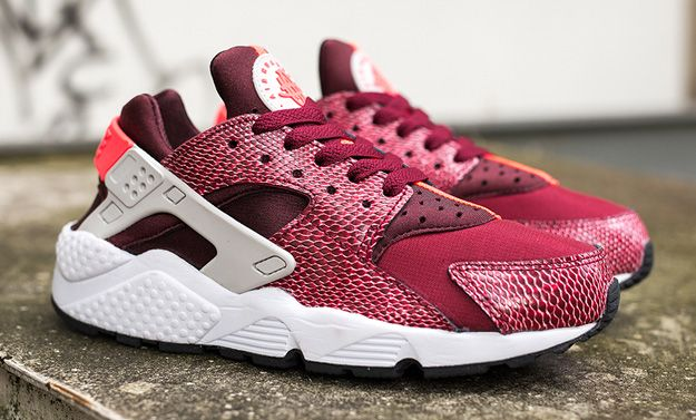 best service 9d950 8961f This dope colorway of the Nike Air Huarache is exclusively for the ladies  and sports a two tone burgundy upper with snakeskin-printed synthetic  leather.