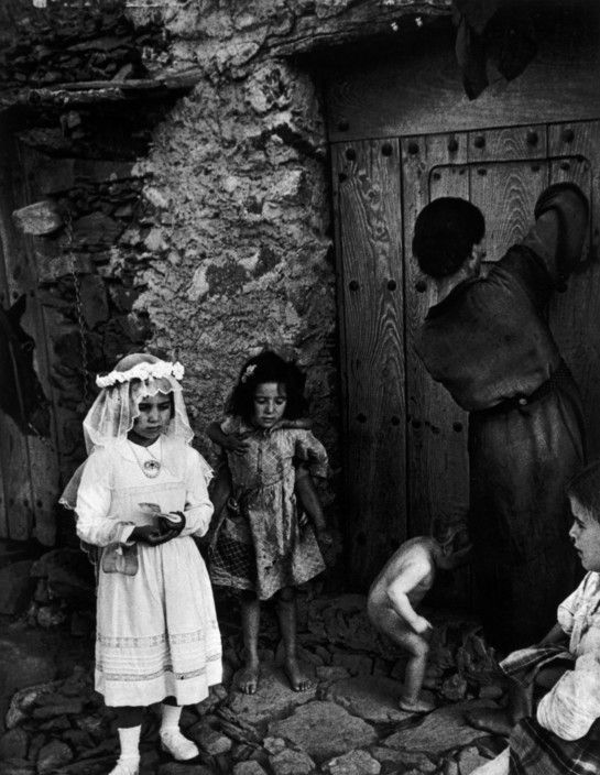 "W. Eugene Smith  SPAIN. Extremadura. Province of Caceres. Deleitosa. 1951. Lorenza Curiel (7 years old), dressed for her First Communion, leaving to go to church. From ""Spanish Village"" photo-essay."