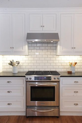 White kitchen cabinets with white subway tile backsplash beveled ...