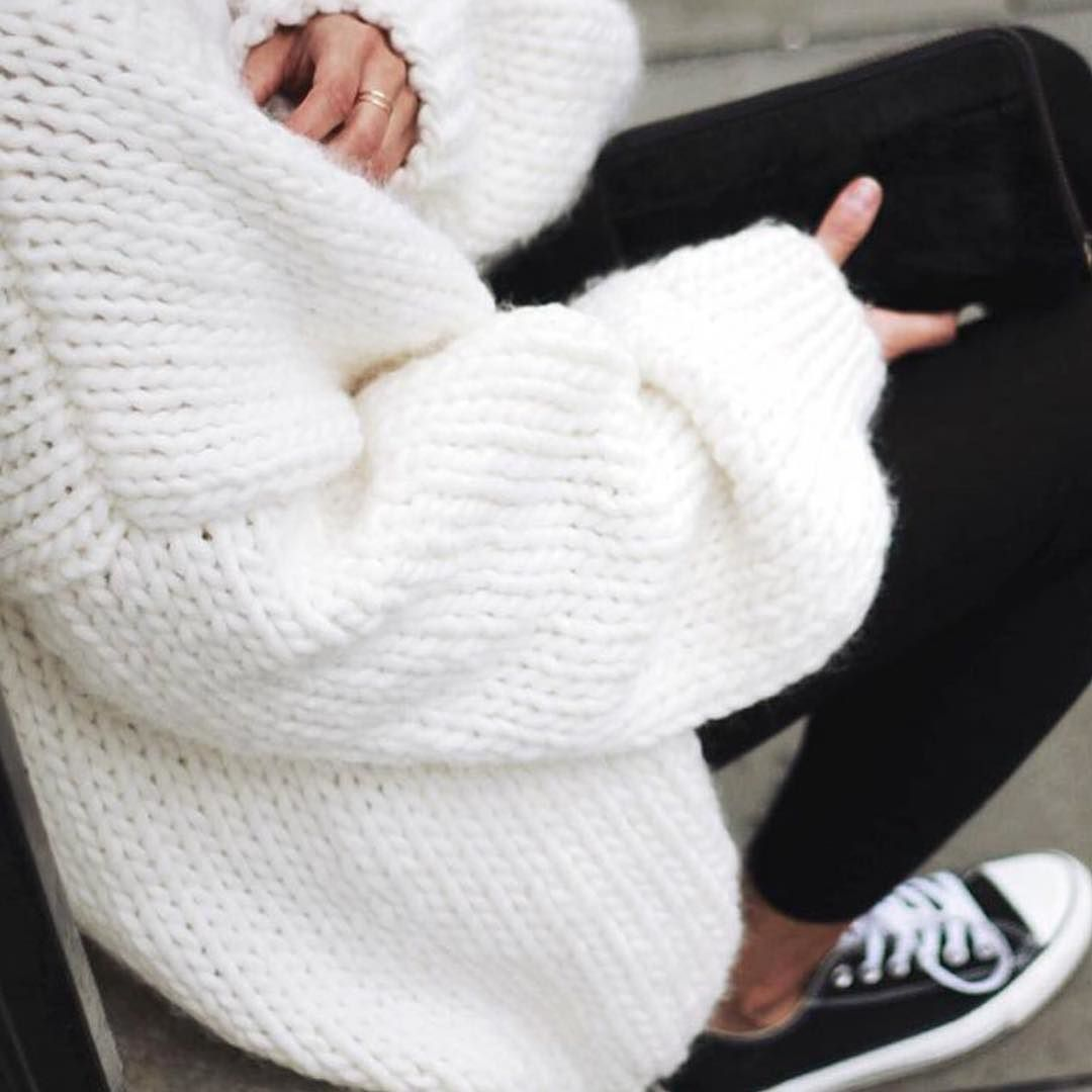 A thick, oversized cream sweater styled over black pants and black ...