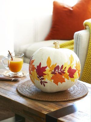 """Decoupage....Trace lawn-gathered leaves onto orange, yellow, and dark red tissue paper; cut tracings out, and stick them to pumpkin using decoupage glue. With a flat-head bristle brush, push from leaves' outer edges toward the centers to pucker paper slightly and create """"veins""""; let dry. Brush a thin layer of glue over pumpkin"""
