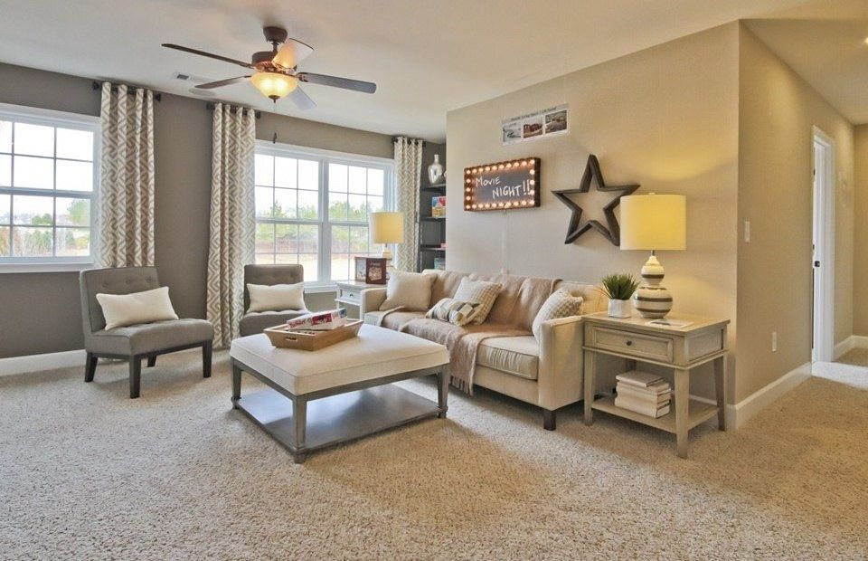living room with medium beige frieze (twisted) carpet, flush lightliving room with medium beige frieze (twisted) carpet, flush light, ceiling fan, high ceiling, carpet