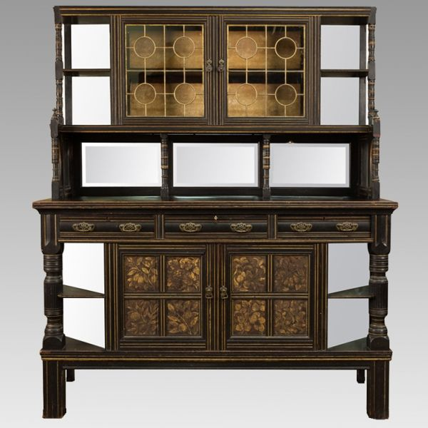 Late 19th Century English Ebonised and Gilded Aesthetic Cabinet Item #5275   Price:  $4295  Circa 1880s English Aesthetic era cabinet has an ebonised finish with gilded floral details on the lower cabinet doors. Top section has open shelves at the sides supported by turned columns and backed with beveled edge mirrors.  The glass front cabinet features an interior shelf with a plate rack and a beveled edge mirror back splash below.