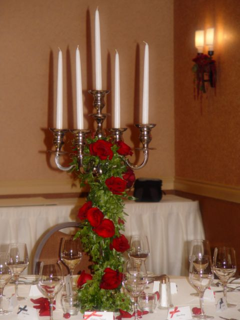 Silver Candelabra Centerpiece With Green Smilax Garlands Red Roses And Red Spray Roses Flower Centerpieces Wedding Candelabra Centerpiece Wedding Centerpieces