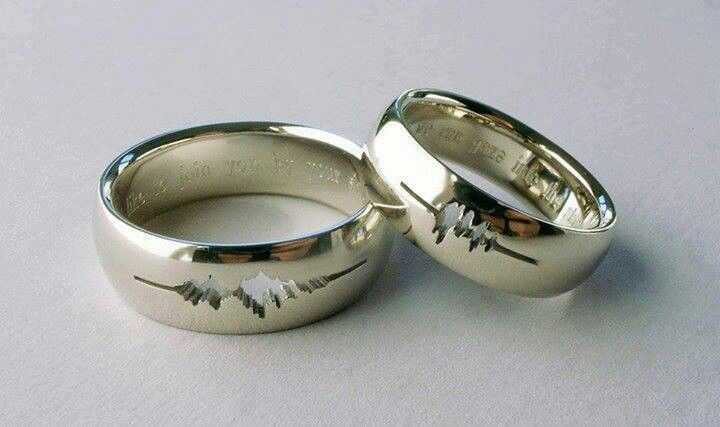 """Wedding rings engraved with waveform of """"I do's""""."""