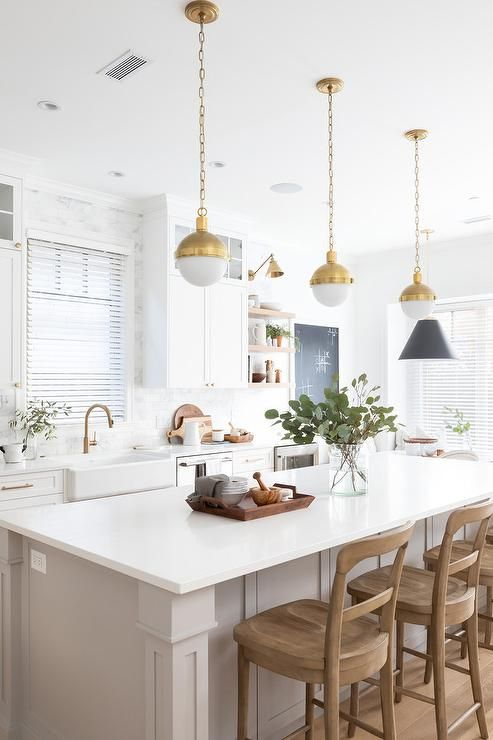 A farmhouse sink paired with a brass gooseneck faucet is mounted beneath a window framed by marble subway surround tiles and flanked by white shaker cabinets positioned under glass front cabinets. #whiteshakercabinets