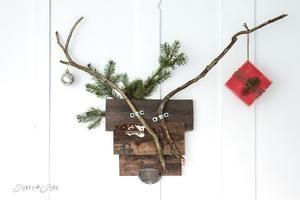 """maak zelf een """"hertenkop"""" van oude planken en twee klemmen voor de gewei-takken en versier met groen, bal en pakje"""