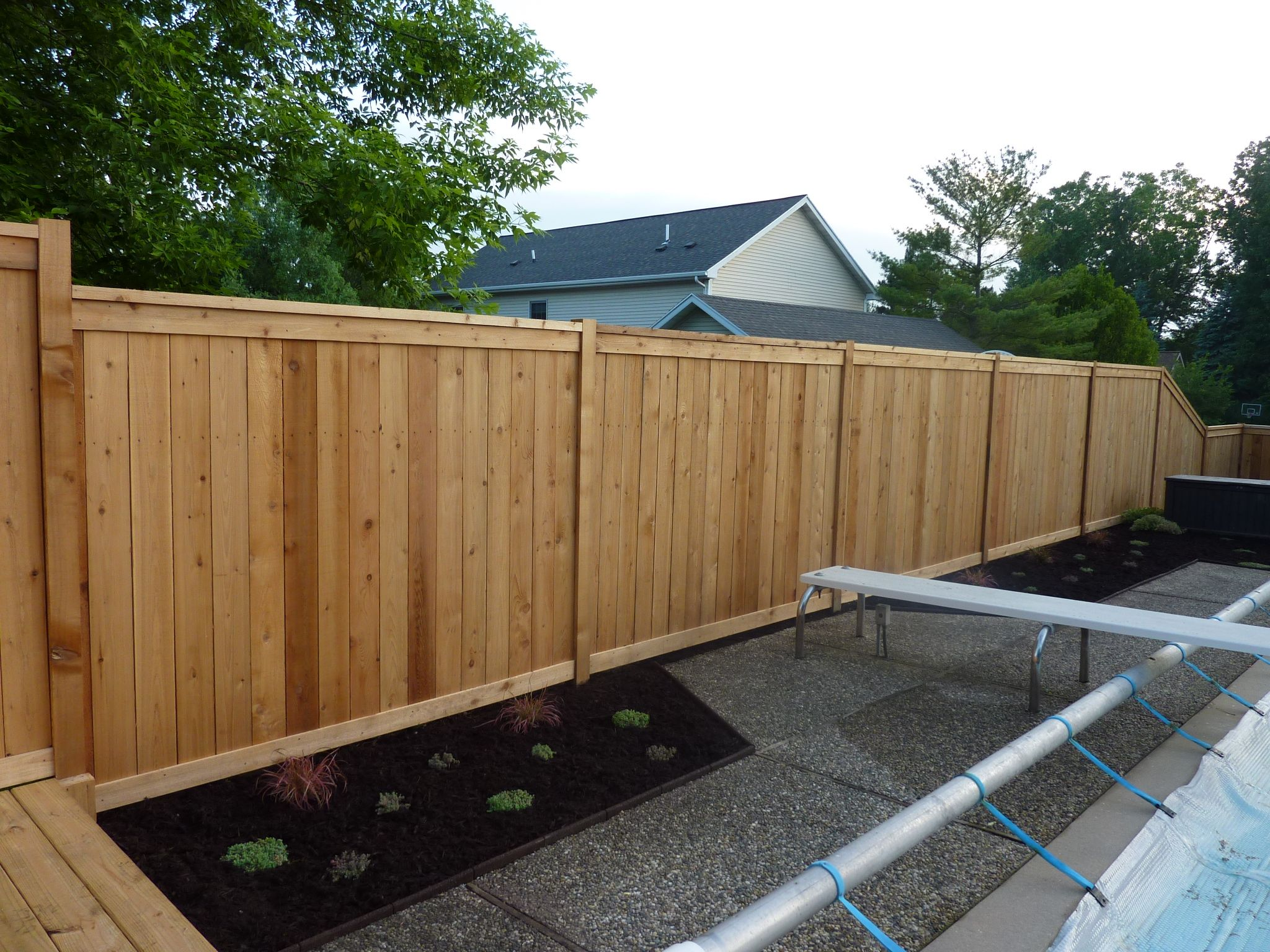 Custom cedar wood privacy fence around pool built on top for Pool privacy screen