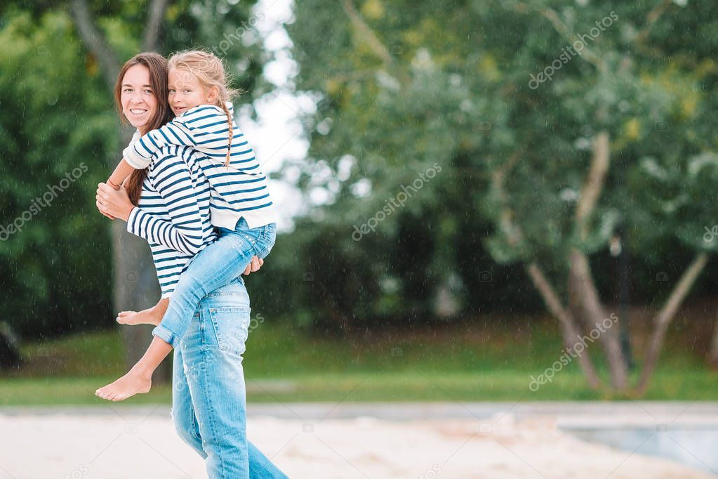 Happy mom and adorable little girl enjoying summer