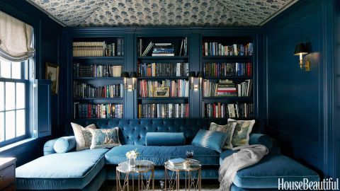 """""""Because the library is small, it lent itself to a rich jewel-box treatment,"""" Whitson says. Woodwork is painted a deep, saturated color, Farrow & Ball's Hague Blue, and the ceiling is tented with a Michael S. Smith Indian block fabric, Jasper. Upholstered in a blue Schumacher silk velvet very close to the color of the walls, the tufted U-shaped sofa — which is all one piece — is where her two teenage children watch movies. """"We call it Big Blue,"""" she says."""